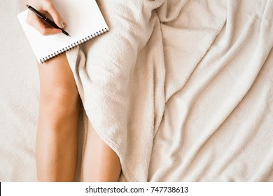Young woman writing something in the notebook in the bed. Peaceful atmosphere.