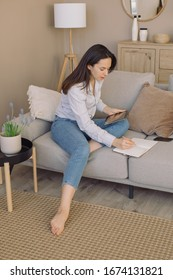 Young woman writing in weekly planner and using an electronic tablet. Home office blogger workspace concept.