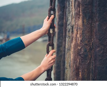 A young woman is yanking a big rusty chain in a shipyard