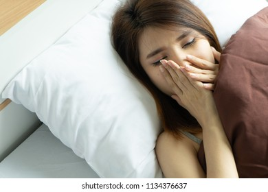 Young woman yawn awakening tired holding alarm clock. wake up early in morning. Girl stop snooze alarm. female waking up sleepy and tired. woman wake up in the morning with alarm clock snooze concept.