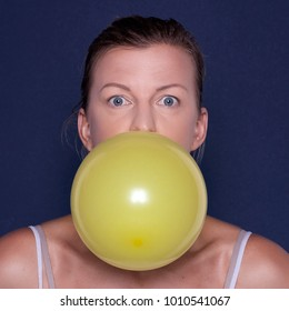 Young woman with yellow balloon in studio on blue background