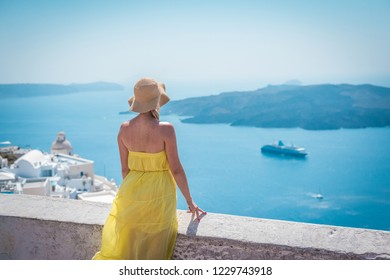 Young woman in a yellow dress and hat admiring the beautiful Mediterranean Sea from the observation deck on Oia, Santorini. Travel and holidays concept.