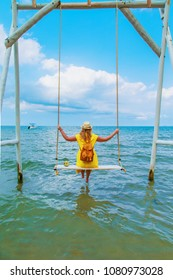 Young woman in a yellow dress is sitting on a swing against the sea. The concept of vacation.