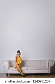Young woman in yellow dress sitting on a couch and wondering.