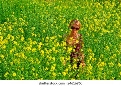 Young woman in the yellow flowers field
