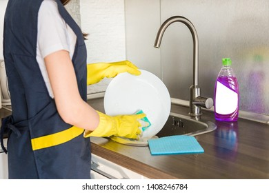 A young woman in yellow gloves washes dishes with a sponge in the sink. House professional cleaning service.