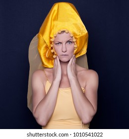 Young woman with yellow hat in studio on blue background