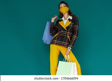 young woman in yellow mask and plaid blazer posing with shopping bags on blue