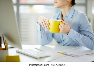 Young woman with yellow mug sitting by desk in office in front of computer monitor