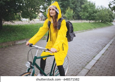 Young woman in yellow raincoat ride bicycle in the rain