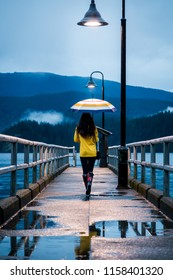 Young woman in a yellow raincoat standing under an umbrella on a rainy day by the ocean