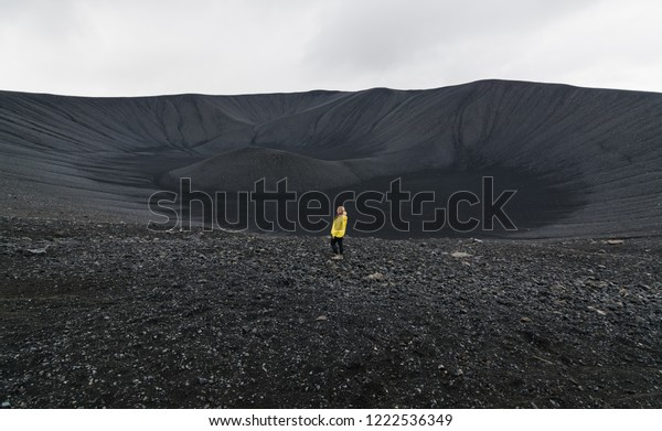 Young woman in yellow raincoat standing in the crater of Hverfjall volcano in Myvatn area, Iceland.