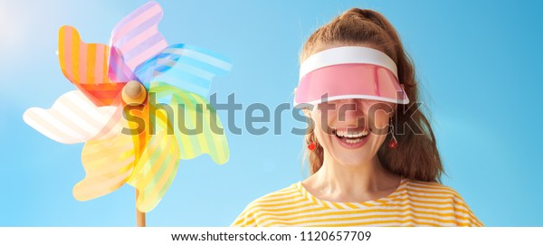 young woman in yellow shirt against blue sky hiding behind sun visor holding colorful windmill
