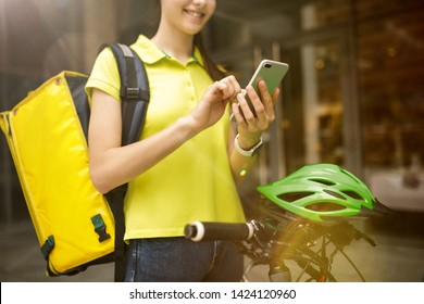 Young woman in yellow shirt delivering food using gadgets to track order at the city's street. Courier using online app for receiving payment and tracking shipping address. Modern technologies.