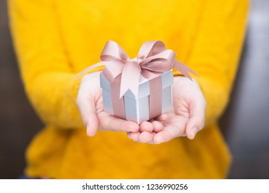 Young woman in yellow swether holding gift box for spacial event. Christmas, birthday, valentine's background concept.