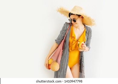 Young woman in yellow swimsuit and straw hat with mesh bag of fruits and cocktail. Summer Vacation concept.