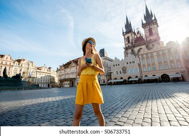 Young woman in yellow walking with smart phone on the old town square in Prague city