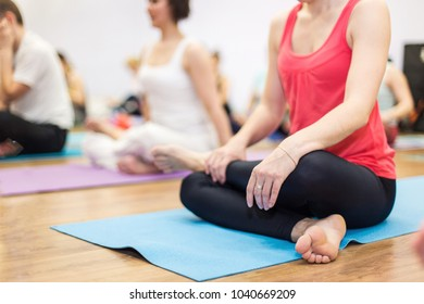 Young woman in yoga class making lotos pose. Healthy lifestyle in fitness club