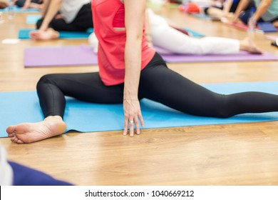 Young woman in yoga class making pose. Healthy lifestyle in fitness club