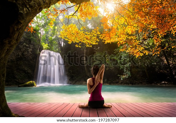 Young woman in yoga Cow face pose sitting near waterfall, Rear view