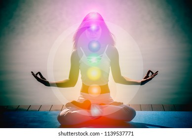 Young woman in yoga meditation hands with seven chakras and Yin Yang symbols.