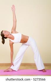 Young woman in a yoga position (Utthita Trikonasana)
