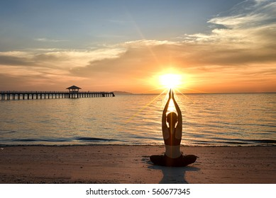 young woman yoga practice on the beach at sunset