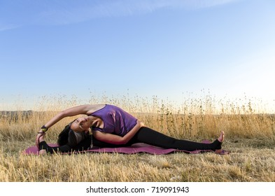 Young woman in yoga stretch, on yoga mat, outdoors. Beautiful scenery, dry grass and sunset . Copy space