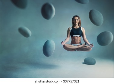 Young woman yogi levitation and meditation concept. Objects flying in room.
