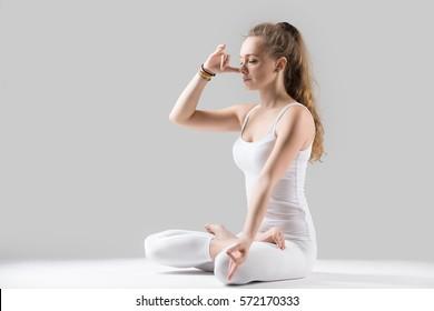 Young woman yogi practicing yoga, sitting in Padmasana, Lotus pose, using Alternate Nostril Breathing, nadi shodhana pranayama, working out, wearing white tank top, pants, full length, grey studio