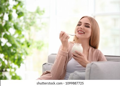 Young woman with yogurt indoors