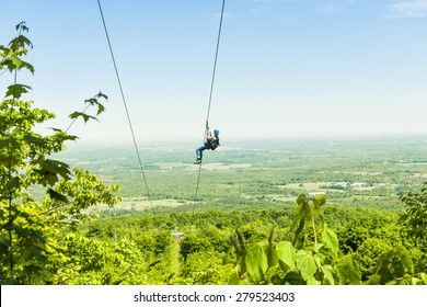 Young woman zip-lining with aerial countryside view at Blue Mountain, Ontario, Canada.
