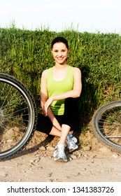 Young womanin sport wear is sitting and resting after cycling on bike.