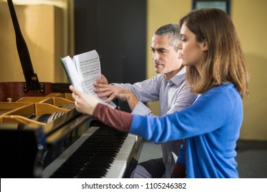 Young womanl having piano class with her teacher.