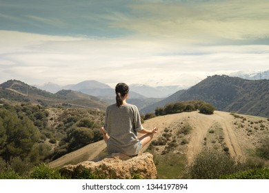 Young womanmeditating in front of Sierra Nevada Mountain