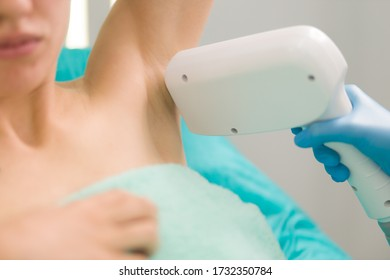 Young womans armpit is under depilation with a special device