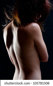 young woman's back turned showing skin texture with low key lighting