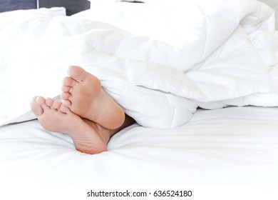 Young woman's bare feet on white blanket
