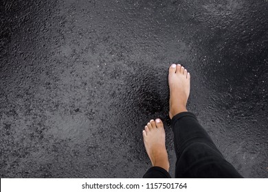 Young woman's barefoot walking on the wet, dark black asphalt after warm rain. Cloudy day in summer. Top view. Empty place for text.