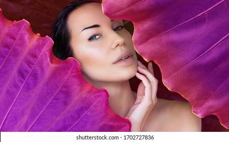 El rostro de una joven rodeada de hojas tropicales de color. La mujer se enfrenta con el maquillaje natural desnudo en un fondo rosado de hojas tropicales. Bienestar y cosmética natural. Pureza y cuidado de la piel. Espacio para texto