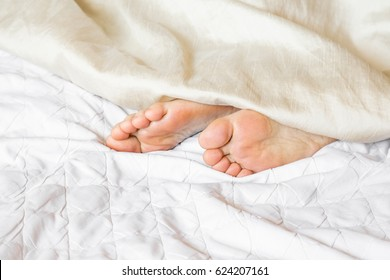 Young woman's feet sleeping almost under the blanket in the bed. Morning waking up.