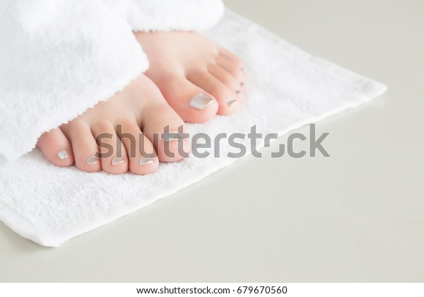Young woman's feet with white, soft towel after washing. Smooth skin.