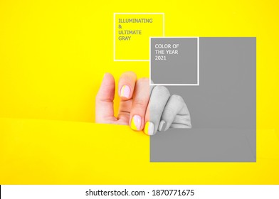Young woman's hand with beautiful manicure on illuminating yellow and gray color background holding bright yellow paper. Color 2021.