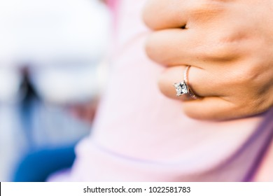 Young woman's hand with diamond engagement ring princess cut, gold outside outdoors on fiance man arm pink shirt love fist