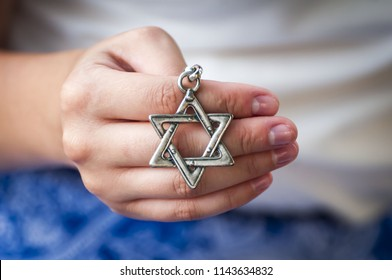 "Young woman's hand holding a David Star (""Magen David"") key chain. The State of Israel, Judaism, Zionism concept image. Conversion to Judaism, giyur concept."