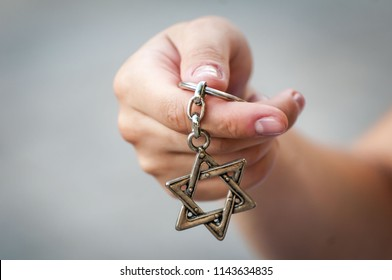 "Young woman's hand holding a David Star (""Magen David"") key chain. The State of Israel, Judaism, Zionism concept image. Conversion to Judaism concept, giyur."