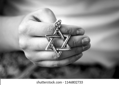 "Young woman's hand holding a David Star, ""Magen David"" key chain. The State of Israel, Judaism, Zionism or Antisemitism concept image. Holocaust Remembrance Day. Never again"