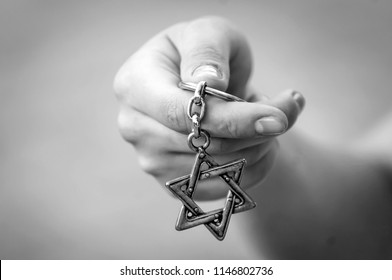 "Young woman's hand holding a David Star, ""Magen David"" key chain. The State of Israel, Judaism, Zionism or Antisemitism concept image. Holocaust Remembrance Day. Never again."
