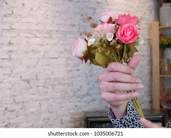 a young woman's hand holding roses bouquet. proposing concept. love background. hand holding roses with white brick wall background and copy space for your text.