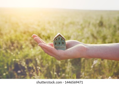 young woman's hand holding small house, natural background, morning sunshine, copy space, sweet home concept
